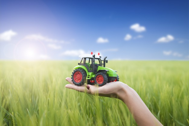 agricultural-machines-concept-farmer-holding-tractor-plastic-toy-field_308072-368